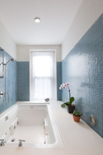 Glass tile, solid-surface bath surround.