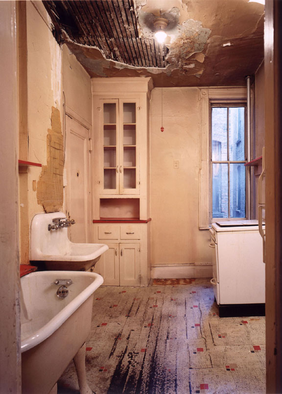 One of the existing kitchens with bathtub in the kitchen before the project removals began.  Photo by David Bogle.